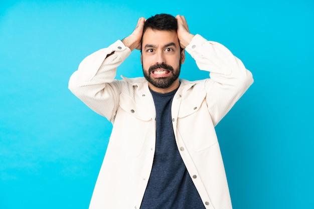 Junger hübscher mann mit weißer cordjacke über blau frustriert und nimmt hände auf kopf