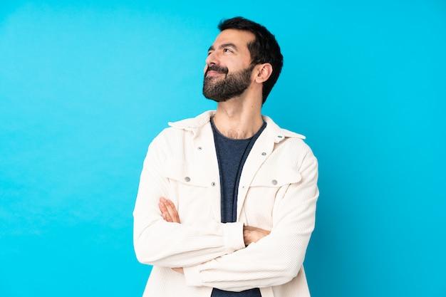 Junger hübscher mann mit weißer cordjacke über blau glücklich und lächelnd