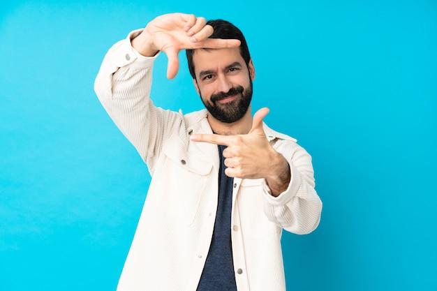 Junger hübscher mann mit weißer cordjacke über blauem fokussiergesicht. rahmensymbol