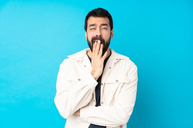 Junger hübscher mann mit weißer cordjacke über blauem gähnen