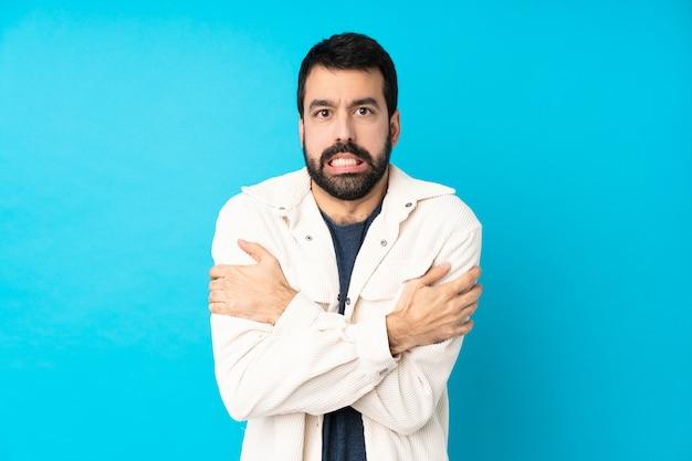 Junger hübscher mann mit weißer cordjacke über blauem gefrieren