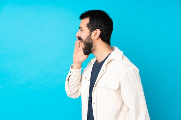 Junger hübscher mann mit weißer cordjacke über blauem schreien mit weit offenem mund zur seite