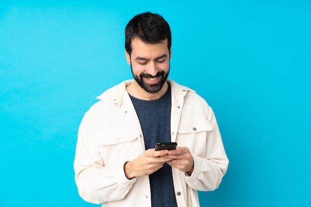 Junger hübscher mann mit weißer kordjacke, die eine nachricht mit dem handy sendet