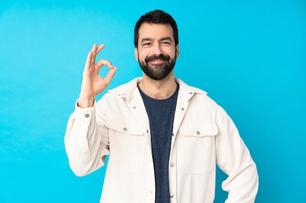 Junger hübscher mann mit weißer kordjacke über blau, das ok zeichen mit den fingern zeigt