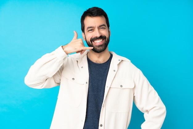 Junger hübscher mann mit weißer kordjacke über blau, das telefongeste macht. rufen sie mich zurück zu unterzeichnen