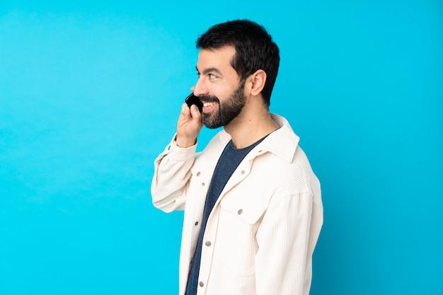 Junger hübscher mann mit weißer kordjacke über blau, der ein gespräch mit dem mobiltelefon mit jemandem hält
