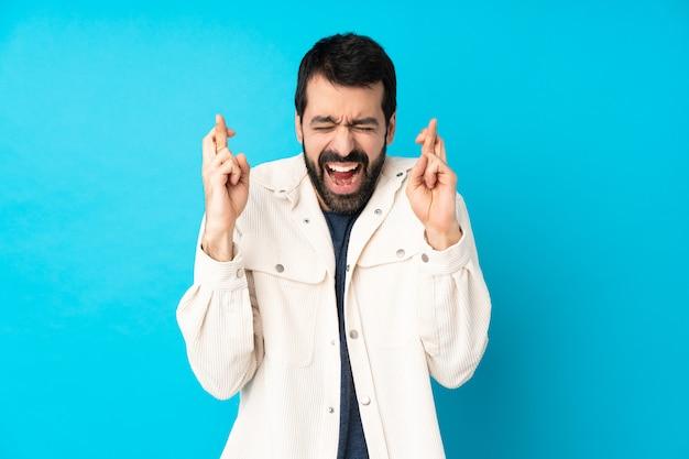 Junger hübscher mann mit weißer kordjacke über blau mit gekreuzten fingern