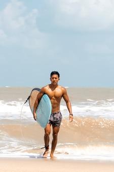 Junger hübscher mann nass am ganzen körper, der leibeigenes brett mit der rechten hand hält und auf dem strand geht
