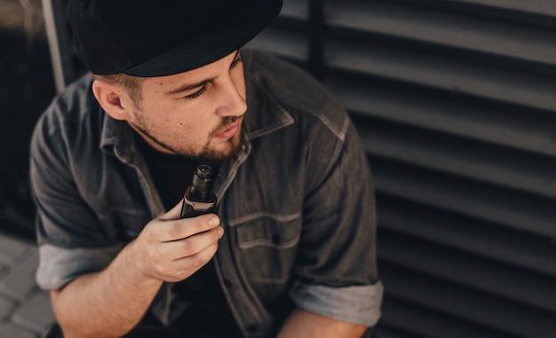 Junger hübscher mann raucht mit vape nahe schwarzer wand