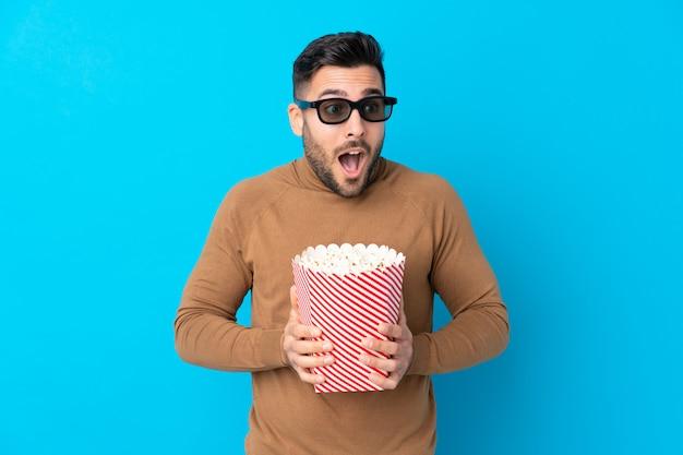 Junger hübscher mann überrascht mit 3d-brille und hält einen großen eimer popcorn
