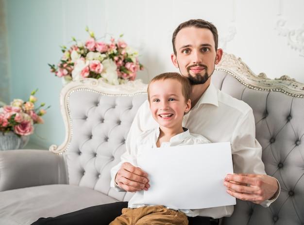 Junger hübscher mann und sohn mit einem papier