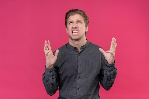 Junger hübscher mann verrückt und verrückt, die mit aggressivem ausdruck schreien