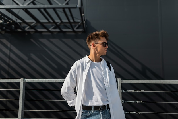 Junger hübscher modellmann mit frisur im stilvollen weißen hemd im t-shirt in den modischen blauen jeans in der trendigen dunklen sonnenbrille mit einem stoffbeutelweg nahe einem grauen gebäude am sonnigen tag. kerl.