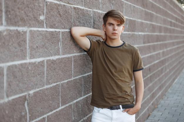 Junger hübscher moderner mann mit modischer frisur in einem grünen stilvollen t-shirt in der trendigen weißen hose, die nahe einer steinernen weinlesewand in der straße aufwirft