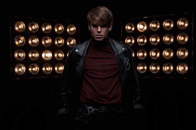 Junger hübscher modischer mann in einer schwarzen lederjacke im burgundergolf in der stilvollen hose, die in einem dunklen studio vor dem hintergrund der hellen elektrischen vintage-orangenbirnen aufwirft. süßer junge. mode.