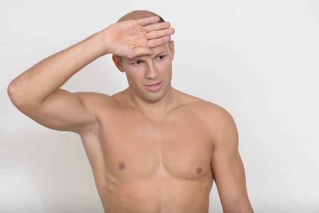 Junger hübscher muskulöser kahlköpfiger mann ohne hemd gegen leerraum