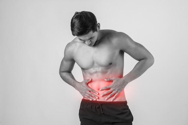 Junger hübscher muskulöser mann hat die bauchschmerzen, die auf weißem hintergrund lokalisiert werden.