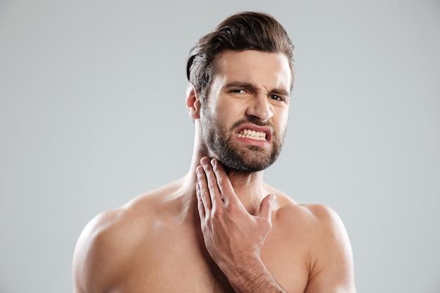 Junger hübscher nackter mann, der sein fce vor dem rasieren erlernt