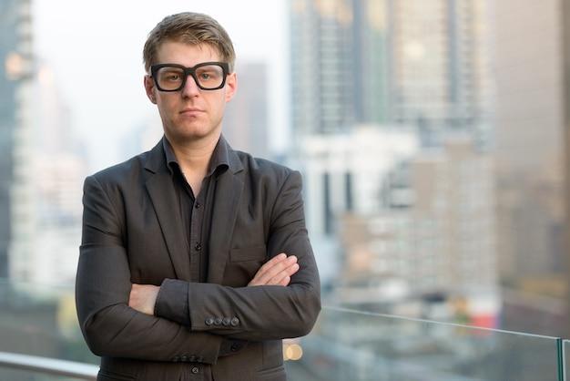 Junger hübscher nerd-geschäftsmann mit verschränkten armen gegen ansicht der stadt