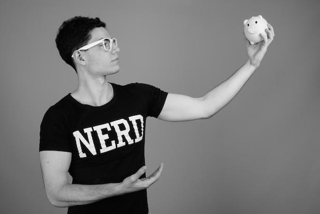 Junger hübscher nerd-mann mit brille gegen graue wand