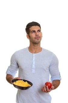 Junger hübscher persischer mann, der schüssel kartoffelchips und roten apfel hält