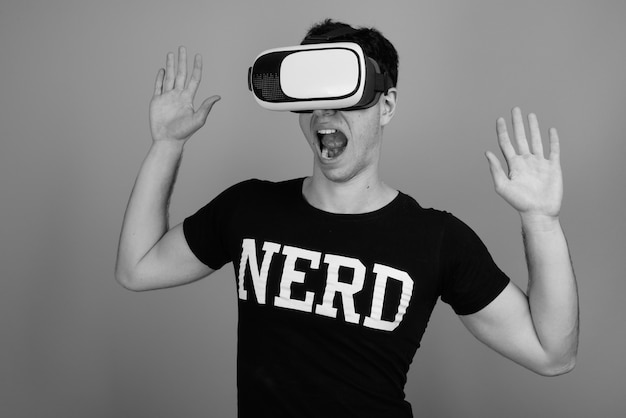 Junger hübscher persischer nerd-mann mit brille gegen graue wand in schwarz und weiß