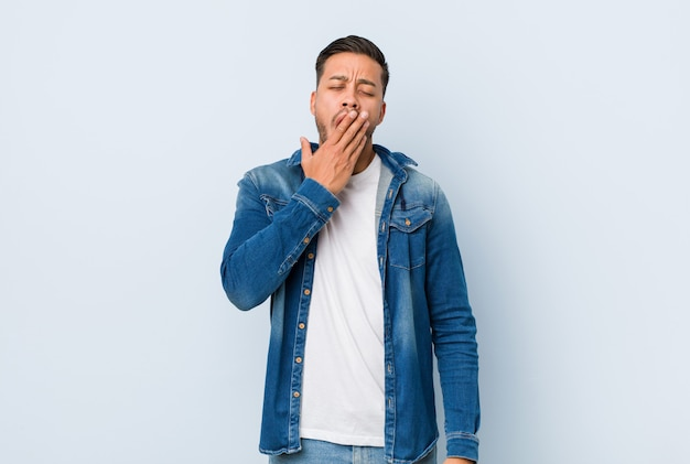 Junger hübscher philippinischer mann, der eine müde geste bedeckt mund mit der hand zeigend gähnt.