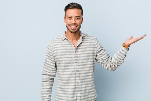 Junger hübscher philippinischer mann, der einen kopienraum auf einer palme zeigt und eine andere hand auf taille hält.