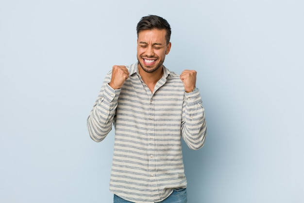 Junger hübscher philippinischer mann, der faust hebt, sich glücklich und erfolgreich fühlt