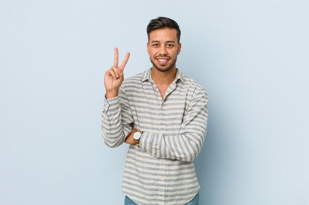 Junger hübscher philippinischer mann, der nummer zwei mit den fingern zeigt.