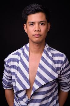 Junger hübscher philippinischer mann gegen schwarze wand