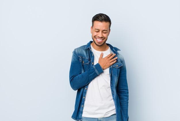 Junger hübscher philippinischer mann lacht laut und hält hand auf brust.