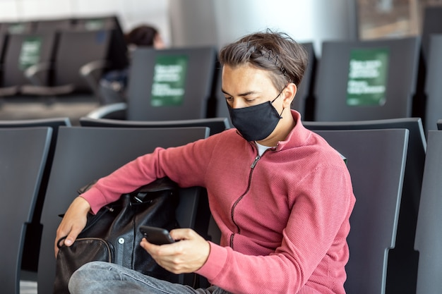 Junger hübscher reisender in einer maske in der lounge des flughafenterminals unter verwendung der smartphone-app im öffentlichen wlan-bereich, nachrichten