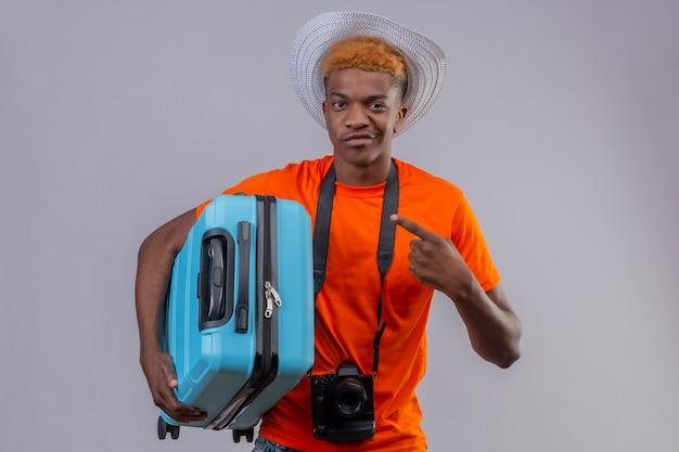 Junger hübscher reisender junge des afroamerikaners im sommerhut, der orange t-shirt mit kamera hält, die reisekoffer hält, der mit dem finger darauf zeigt, kamera mit skeptischem lächeln weißem hintergrund betrachtend