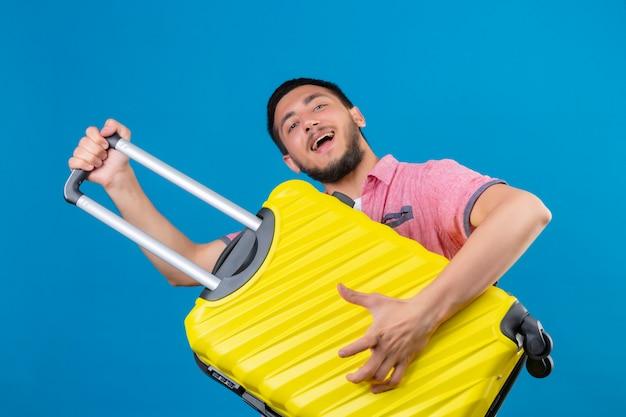 Junger hübscher reisender kerl, der koffer hält, der als eine gitarre schaut, die freudig mit glücklichem gesicht steht, das über blauem hintergrund steht