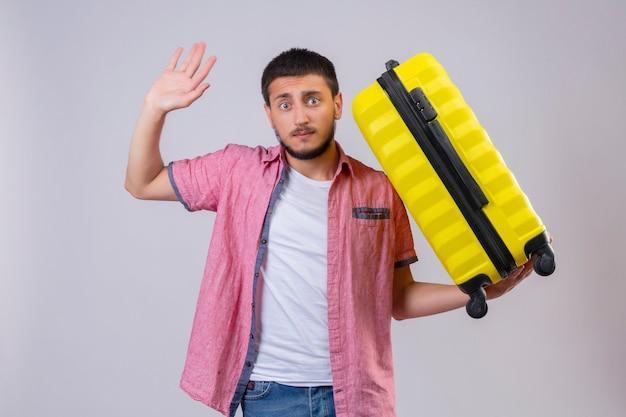Junger hübscher reisender kerl, der koffer hält, der hand in der übergabe betrachtet, kamera mit verwirrendem ausdruck auf gesicht stehend über weißem hintergrund betrachtet