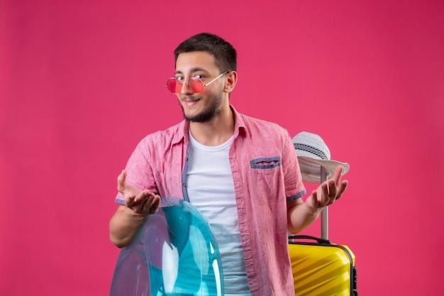 Junger hübscher reisender kerl, der sonnenbrille hält, die aufblasbaren ring hält, der mit reisekoffer steht und kamera betrachtet, die schlau mit armen lächelt, die über rosa hintergrund erhoben werden