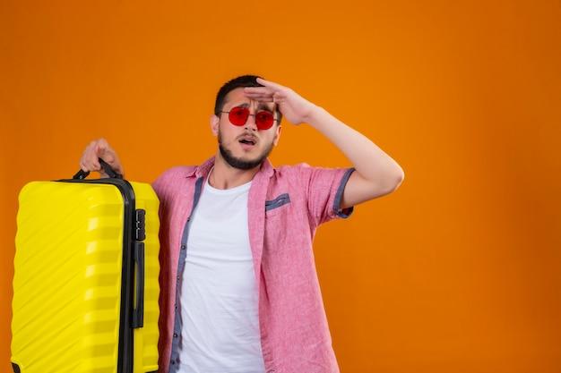 Junger hübscher reisender kerl, der sonnenbrille hält, koffer hält, der weit weg mit hand schaut, um etwas mit verwirrendem ausdruck zu schauen, der über orange hintergrund steht