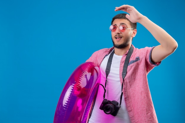 Junger hübscher reisender kerl, der sonnenbrillen steht, die mit aufblasbarem ring stehen und beiseite winken mit hand glücklich und positiv über blauem hintergrund winken