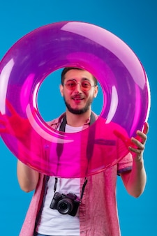 Junger hübscher reisender kerl, der sonnenbrillen trägt, die mit aufblasbarem ring stehen, der durch diesen ring schaut, der fröhlich über blauem hintergrund lächelt