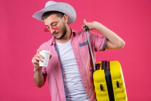 Junger hübscher reisender kerl im sommerhut, der sonnenbrille hält, die koffer und tasse kaffee hält, die zuversichtlich stehen über rosa hintergrund stehen
