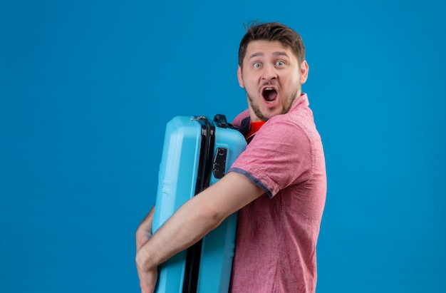 Junger hübscher reisender mann, der blauen koffer hält, der mit weit offenem mund schockiert ist