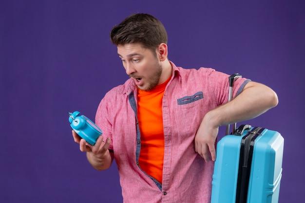 Junger hübscher reisender mann, der blauen koffer hält und wecker in seiner hand betrachtet
