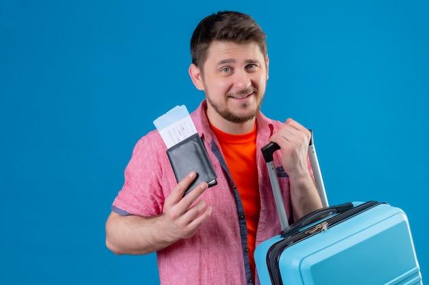 Junger hübscher reisender mann, der flugscheinen und koffer positiv lächelnd hält