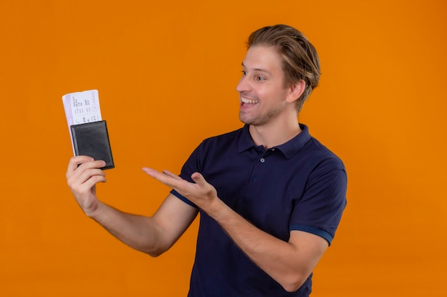 Junger hübscher reisender mann, der flugtickets hält, die mit arm der hand präsentieren, die zu ihnen mit lächeln auf gesicht über orange hintergrund schauen
