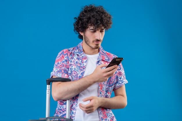 Junger hübscher reisender mann, der handy hält und es mit koffer auf isolierter blauer wand mit kopienraum betrachtet