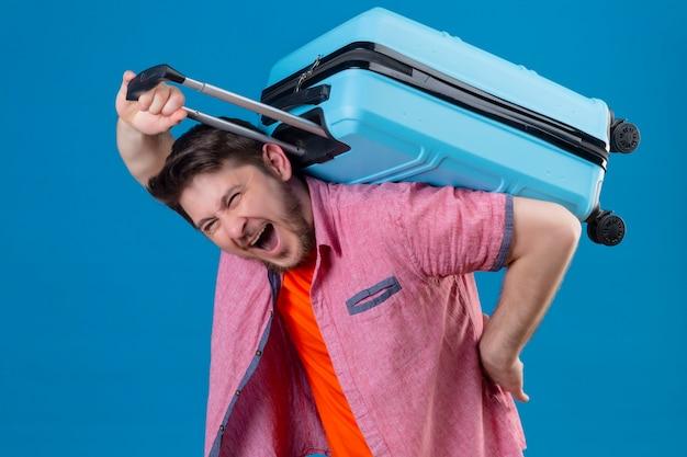 Junger hübscher reisender mann, der koffer auf seinem rücken hält, der unwohl sieht, das unter schwerem gewicht leidet, das über blauer wand steht