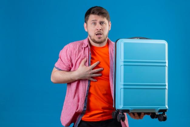 Junger hübscher reisender mann, der koffer emotional und besorgt mit angstausdruck auf gesicht steht, das über blauer wand steht