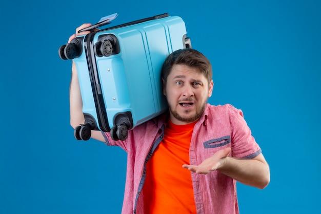Junger hübscher reisender mann, der koffer hält, der verwirrt sehr emotional und besorgt steht und über blauer wand steht