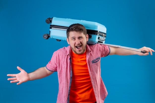 Junger hübscher reisender mann, der koffer verrückt und verrückt hält, der mit wütendem ausdruck schreit